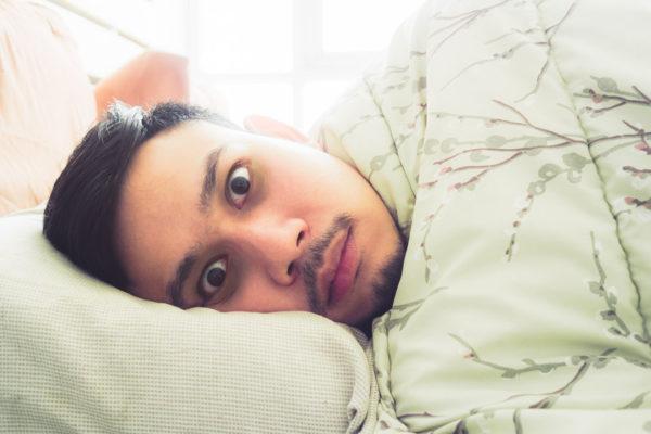 mężczyzna w łóżku z szeroko otwartymi oczami