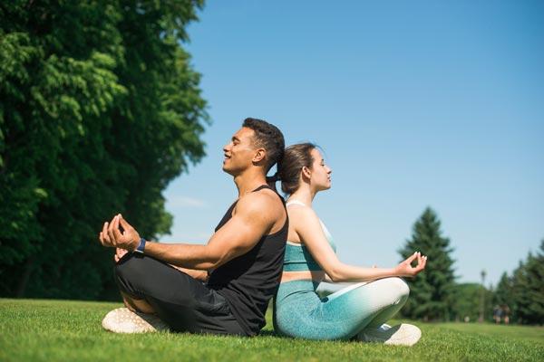 para młodych ludzi medytuje w parku siedząc tyłem do siebie