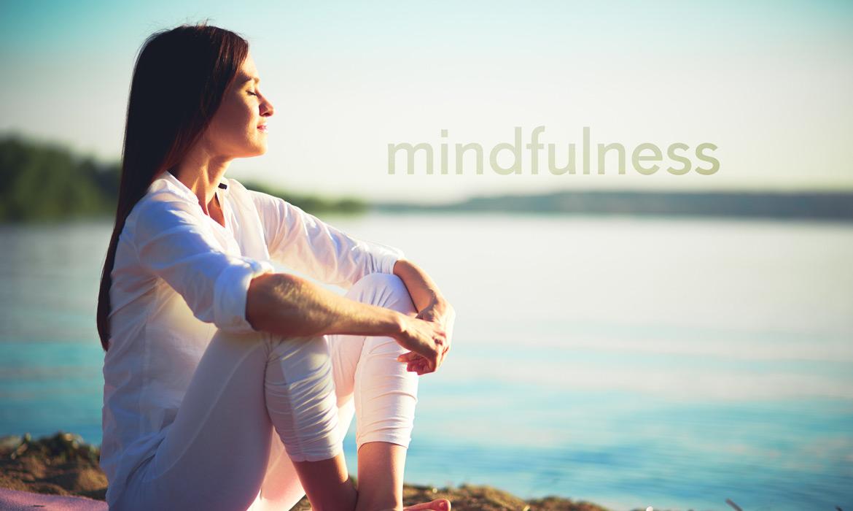 kobieta medytująca siedząc nad wodą