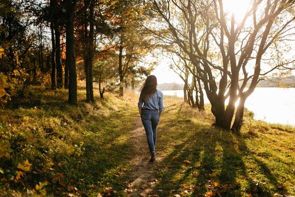 młoda kobieta spaceruje leśną ścieżką nad jeziorem w słoneczny dzień
