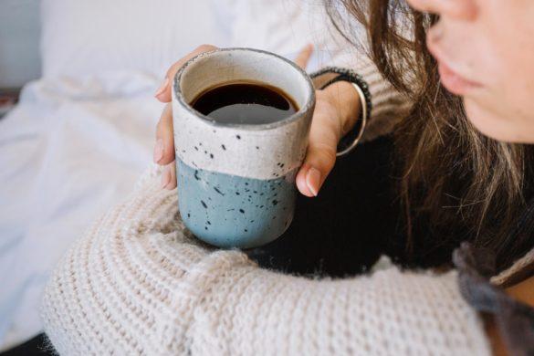 ciemnowłosa kobieta siedząca na łóżku trzymająca kubek z kawą