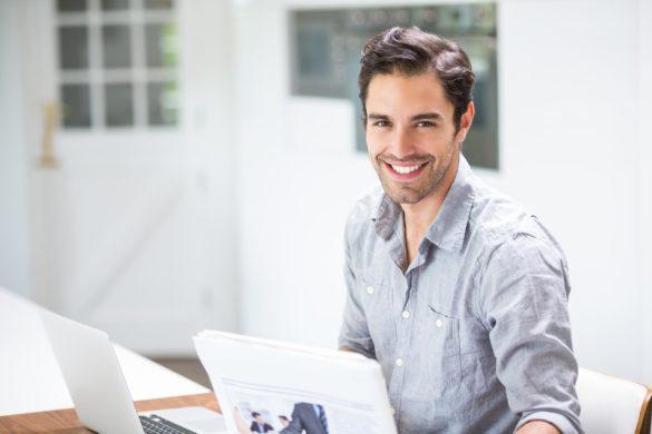 młody uśmiechnięty męczyzna siedzi przy biurku