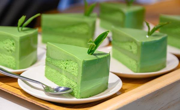 kawałki zielonego sernika z matcha na spodkach ustawionych na blacie stołu