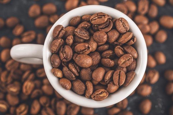 ziarna kawy w białym kubku