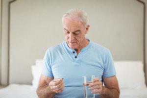 starszy mężczyzna przyjmuje tabletkę z hormonem dhea