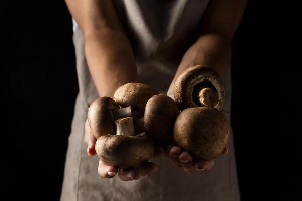 kobieta trzymająca w wyciągniętych dłoniach grzyby