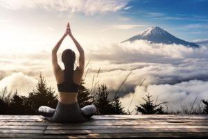 młoda szczupła kobieta praktykująca medytację w górach