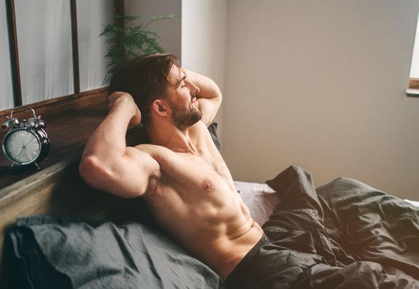 młody muskularny mężczyzna o poranku przeciąga się wstając z łóżka