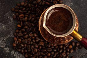 tradycyjnie parzona turecka kawa na tle ziaren kawy